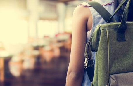 afbeelding van een leerling met rugtas die een klaslokaal binnen gaat