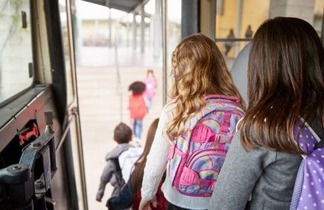 twee meisjes stappen uit een schoolbus
