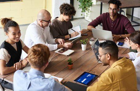 zeven mensen vergaderen aan een houten tafel